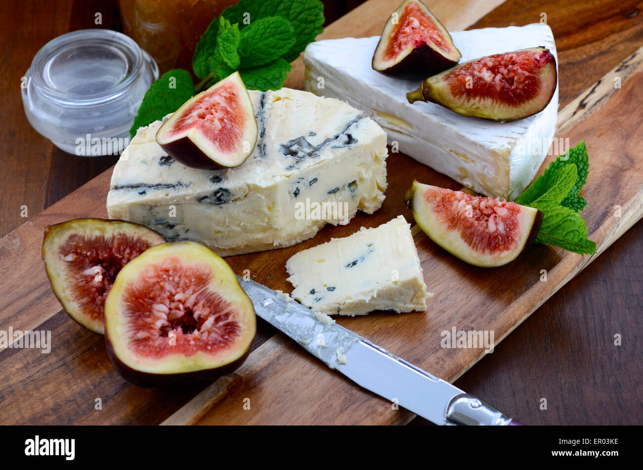 Fresh figs on wooden cutting chopping board with jar of fig jelly preserve and gourmet cheese on dark wood rustic - Stock Image