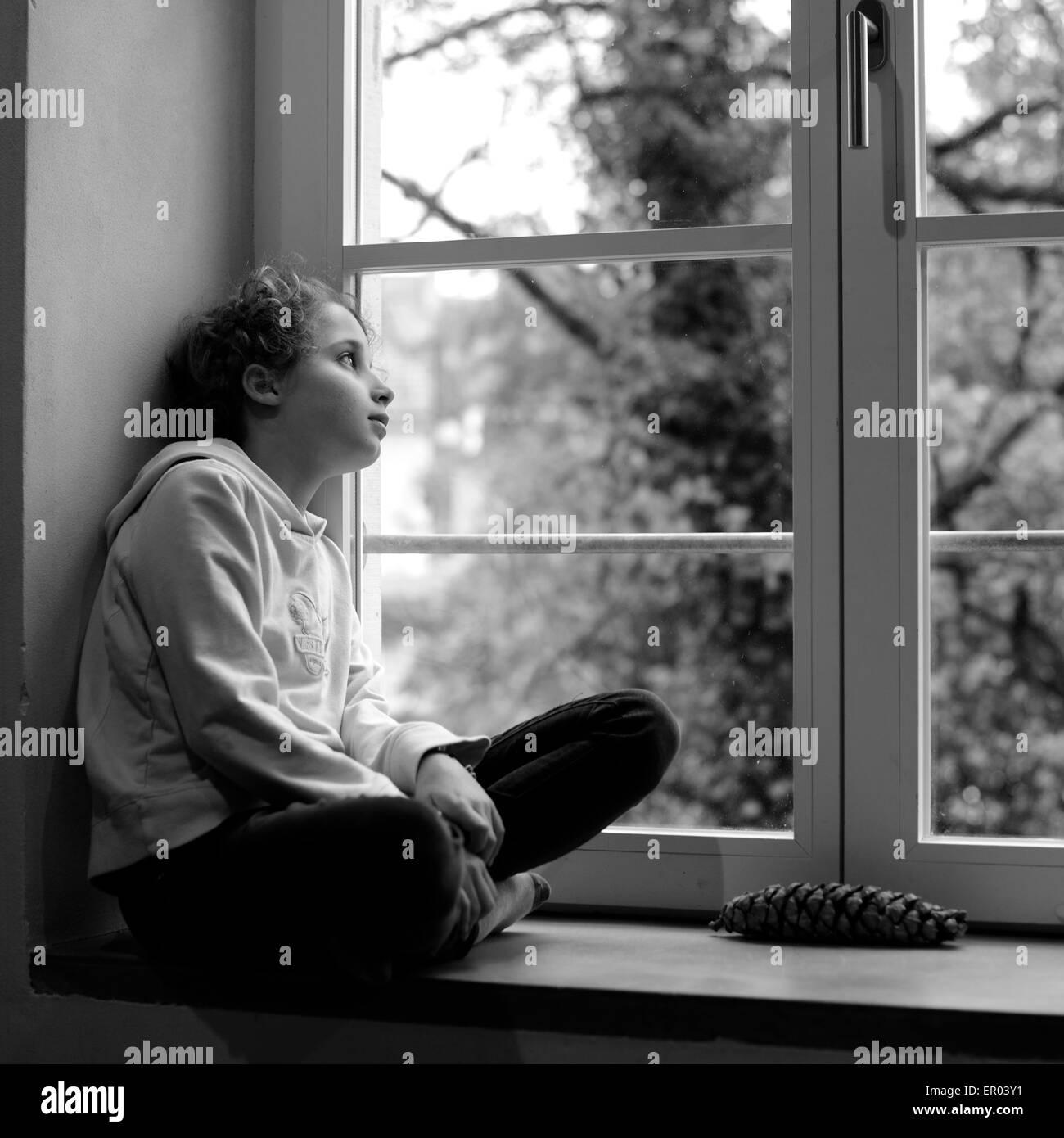 Girl looking throug a window stock image