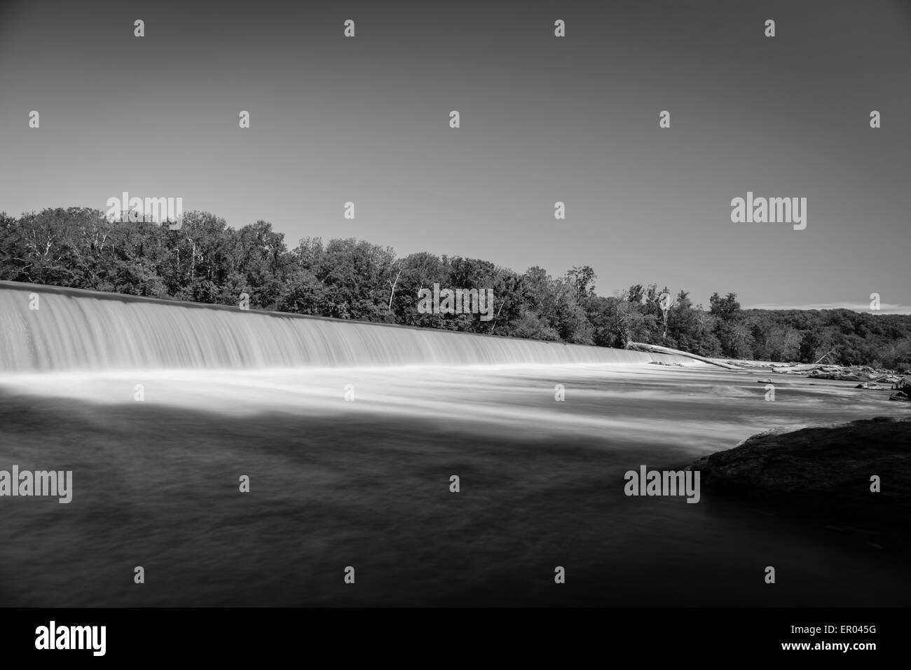 Long exposure of silky water pouring over man made dam in black and white Stock Photo