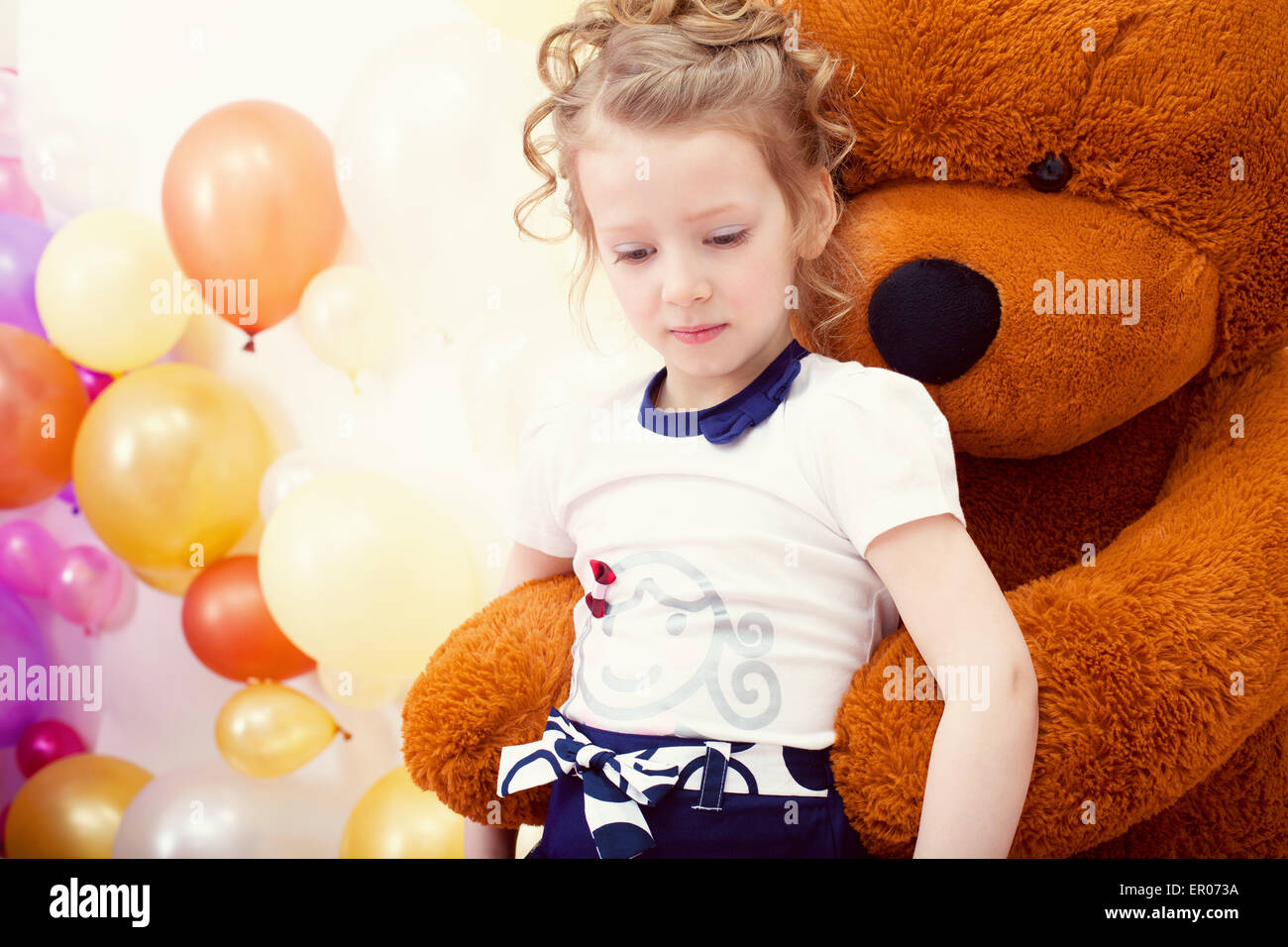 Cute girl posing in embrace with big teddy bear - Stock Image