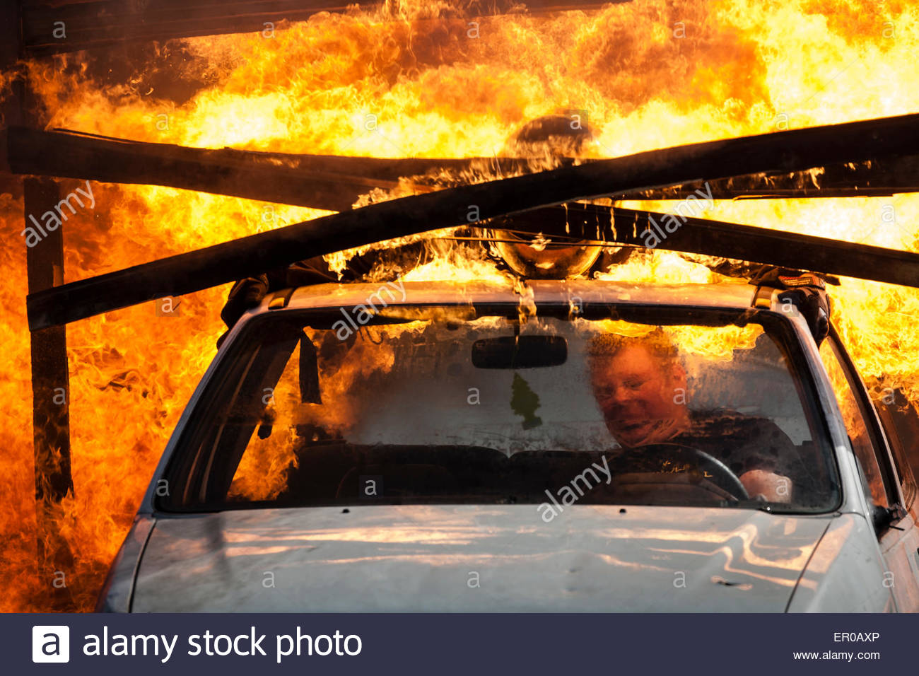 car driving through a fire wall during a stuntshow Stock Photo