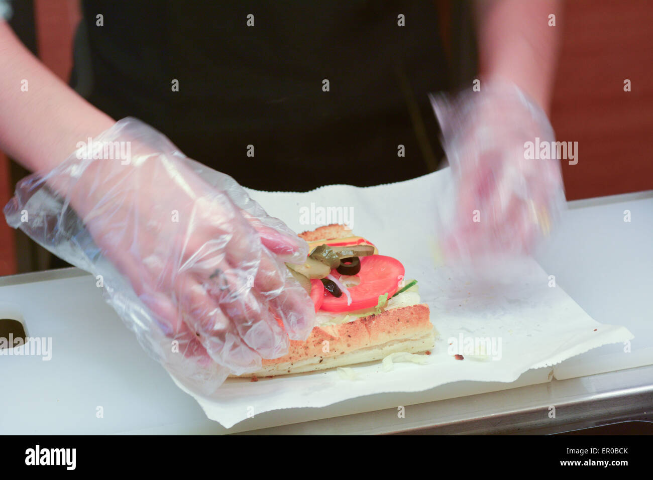 SHANGHAI, CN - MAR 15 2015:Hands of a SUBWAY worker prepare SUBWAY sandwich. It's the largest single-brand restaurant - Stock Image