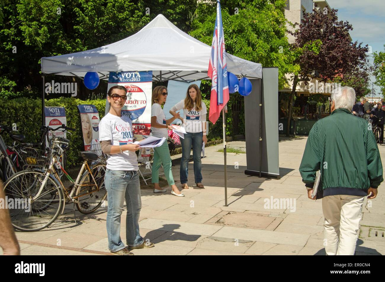 VENICE, ITALY - MAY 24, 2015:  A smiling supporter of the mayoral candidate Francesca Zaccariotto handing out leaflets - Stock Image