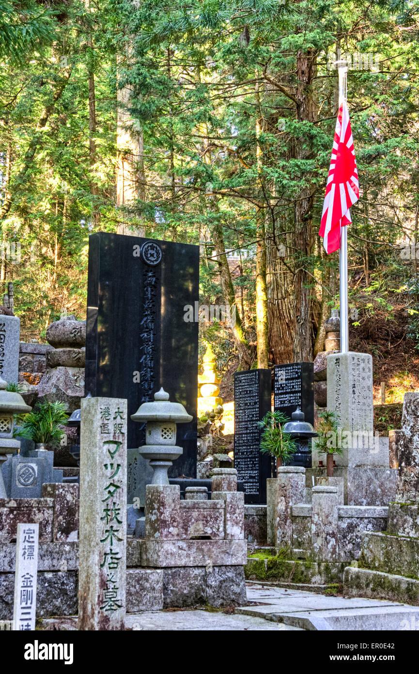 Japan, Koyasan, Okunoin cemetery. World war two Japanese war memorial with Rising Sun flag. Sunlit forest of cedars - Stock Image