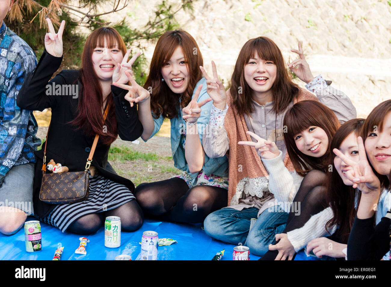 Japan, Shukugawa, cherry blossom party. Group of teenage girls sitting and posing for viewer, big smiles, peace - Stock Image