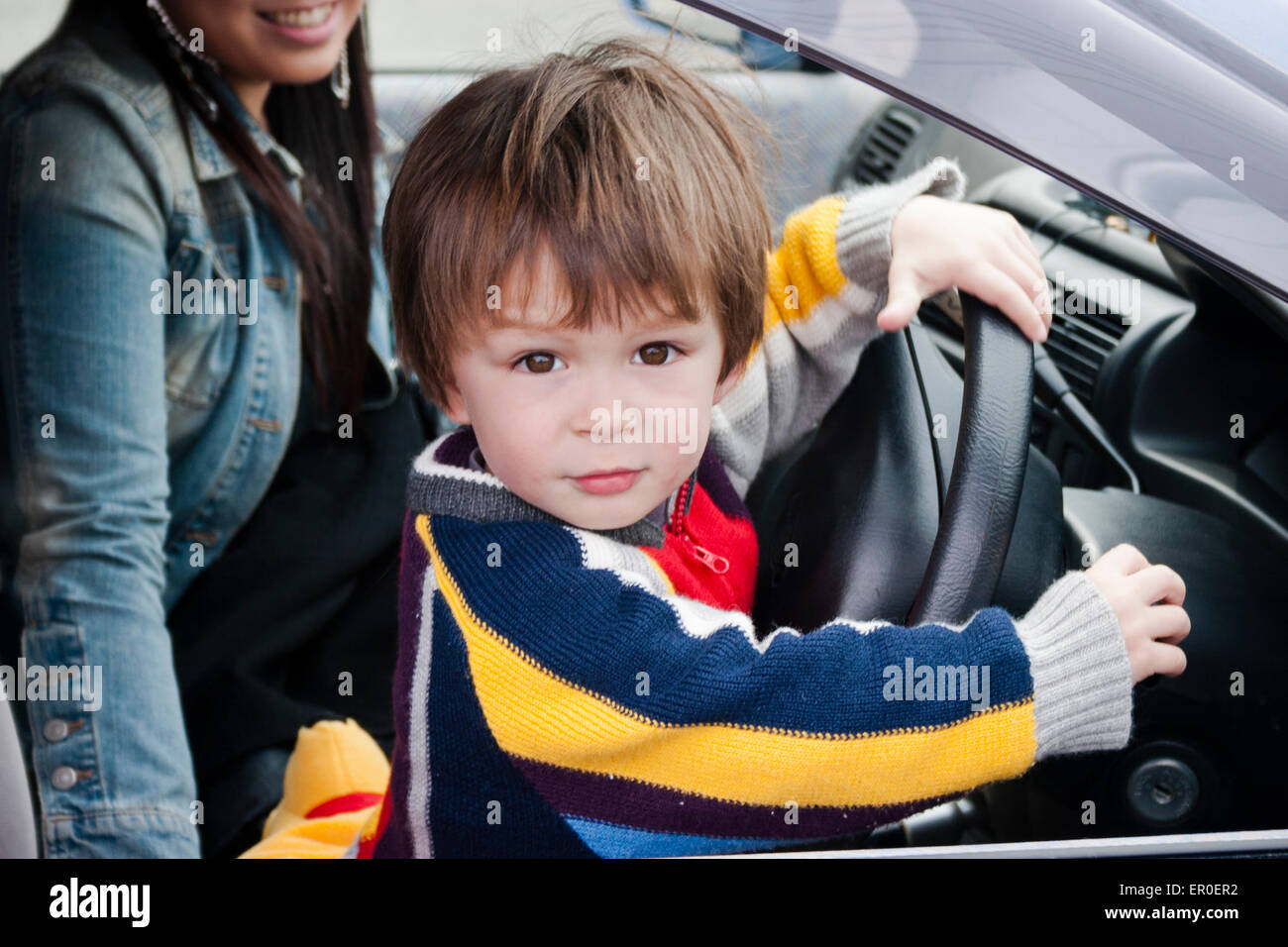 3 4 Year Old Caucasian Child Boy Side View Sitting In Car Seat Both Hands On Steering Wheel Face Turned To Viewer