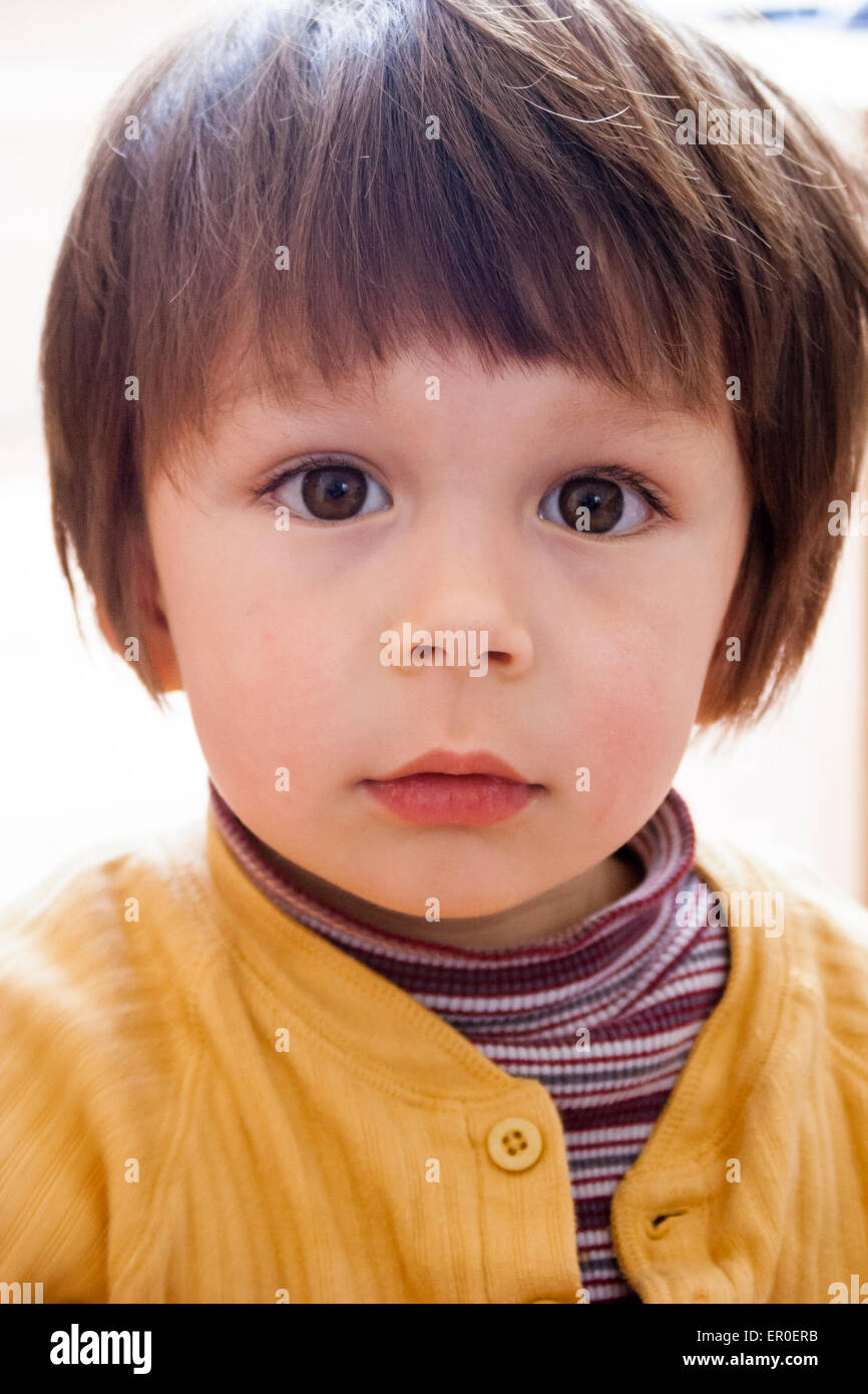 3 or 4 year old Caucasian child, boy. Half length, facing, looking at view, uncertain, unsure expression - Stock Image