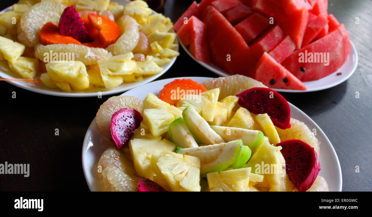 Tropical fruits sliced slices on the three saucers - Stock Image