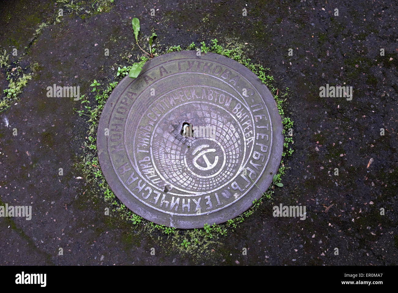 Sewer manhole cover with Russian script at the former KGB prison now the museum of Genocide Victims in the city - Stock Image