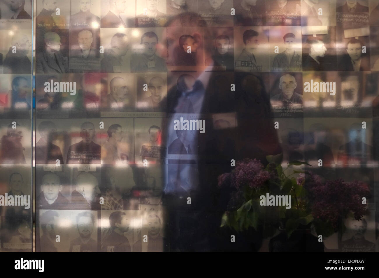 A person is seen through mugshots of prisoners at the the former KGB prison now the museum of Genocide Victims in - Stock Image