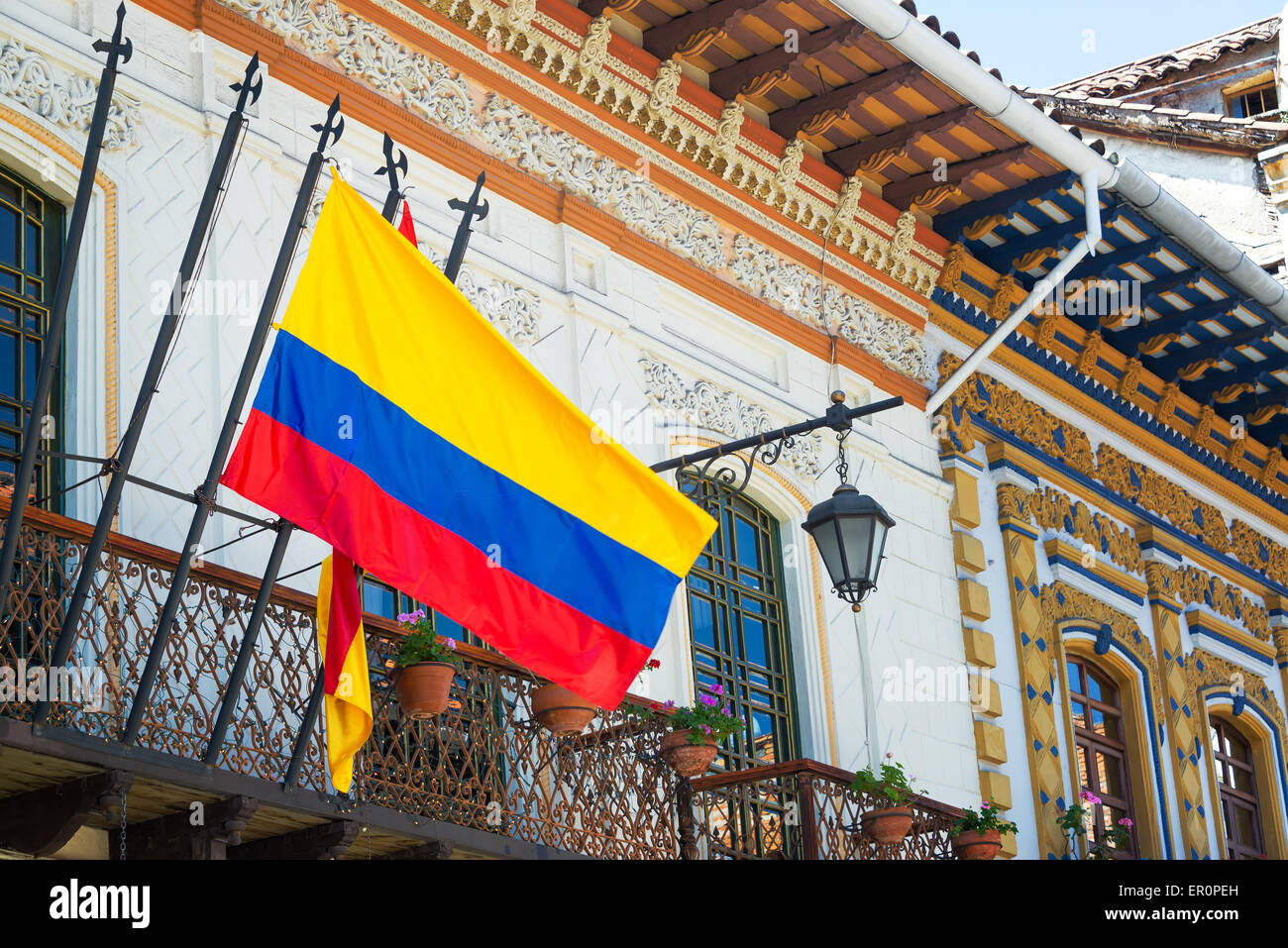 Historic buildings in Cuenca, Ecuador with a Ecuadorian flag in the foreground - Stock Image