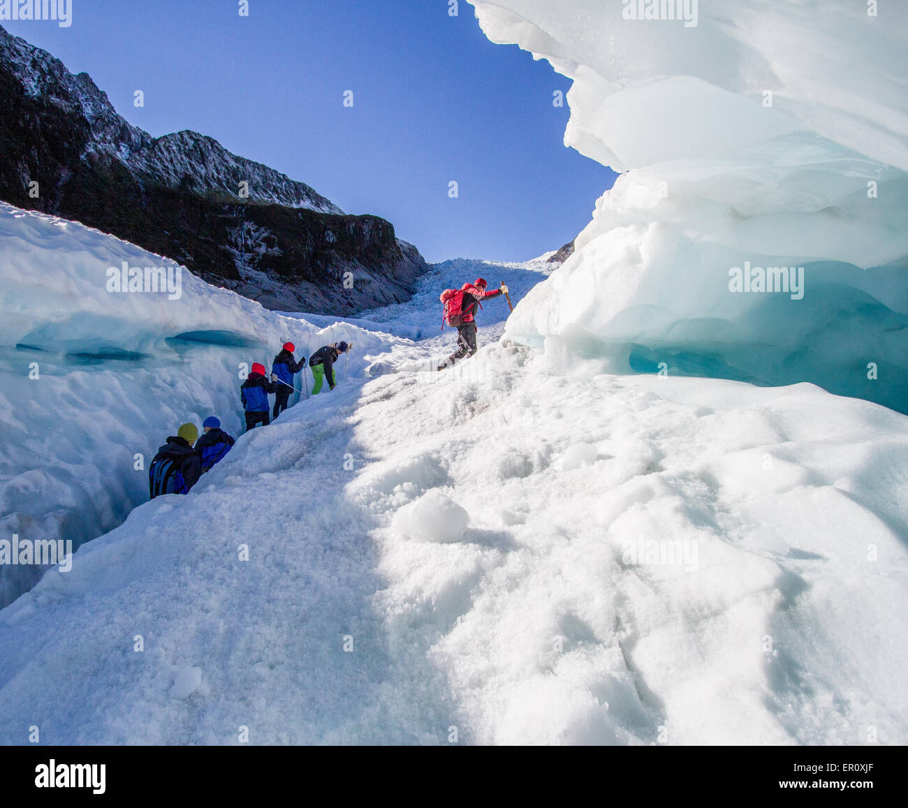 Climbing party and their guide negotiate an ice crevasse and overhang on Fox Glacier in the Southern Alps New Zealand - Stock Image