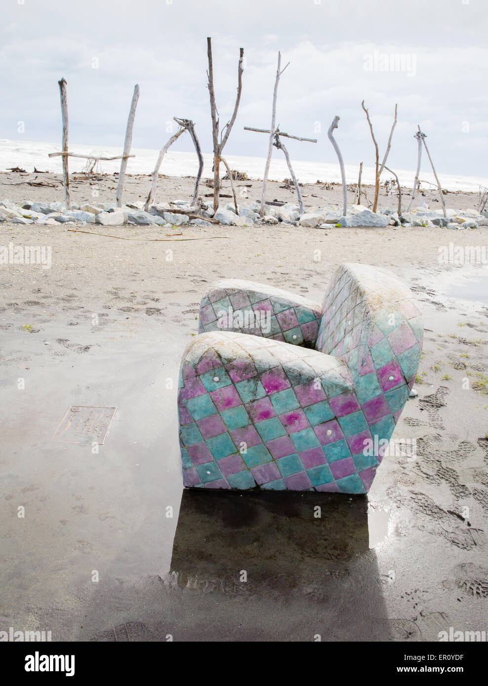 Armchair sculpture and flotsam town sign on the beach at Hokitika on the west coast of South Island New Zealand - Stock Image