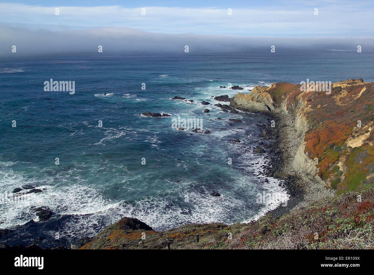 A gray fog bank rolls in over the blue Pacific Ocean along the rugged coast at Big Sur in central California, USA. - Stock Image