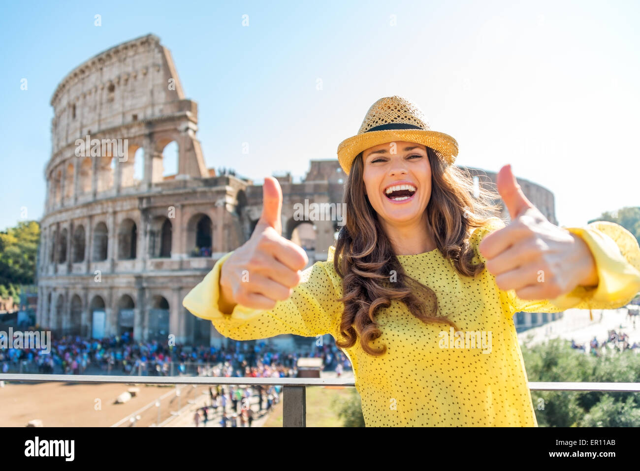 A laughing woman tourist is giving two thumbs up to being a tourist in Rome. In the distance, the Colosseum and - Stock Image