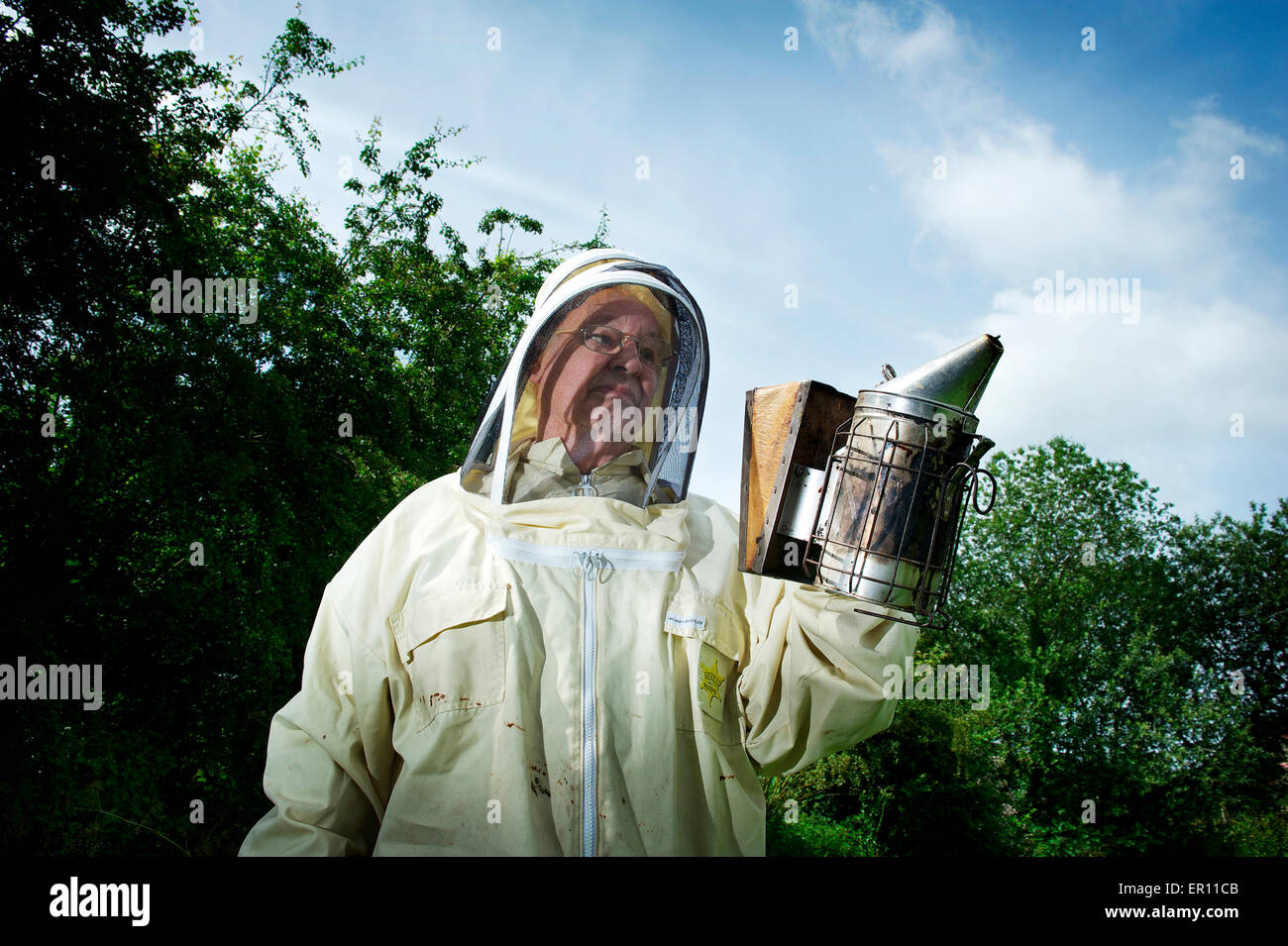 Bob Spruce holding the smoker, ready to inspect his hives - Stock Image