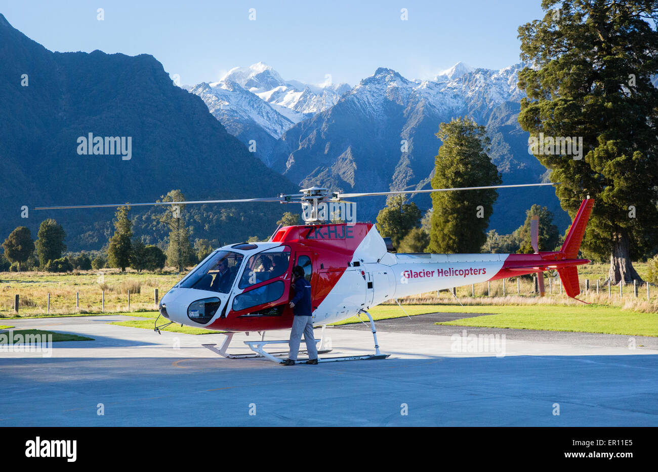 Helicopters on the pad at Fox village airlifting walkers onto Fox Glacier in the Southern Alps of New Zealand - Stock Image