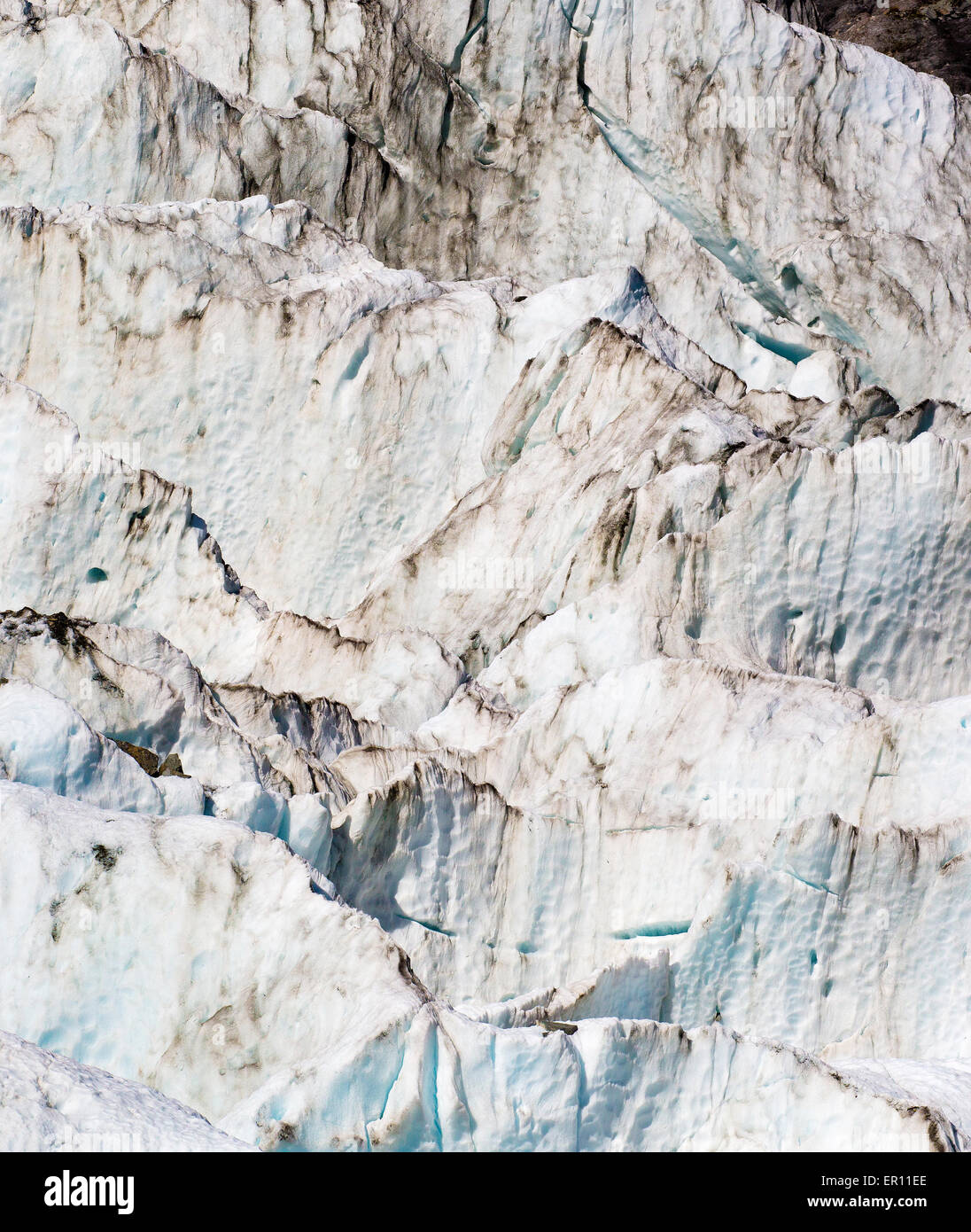 Patterns of eroded rock debris in large blocks of blue ice on the lateral section of Fox Glacier in South Island - Stock Image