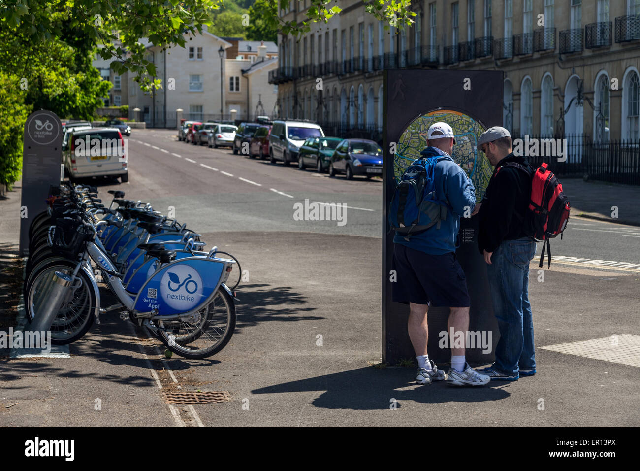 Two tourist men reading an information map notice next to electric hire bikes in City of Bath, UK - Stock Image