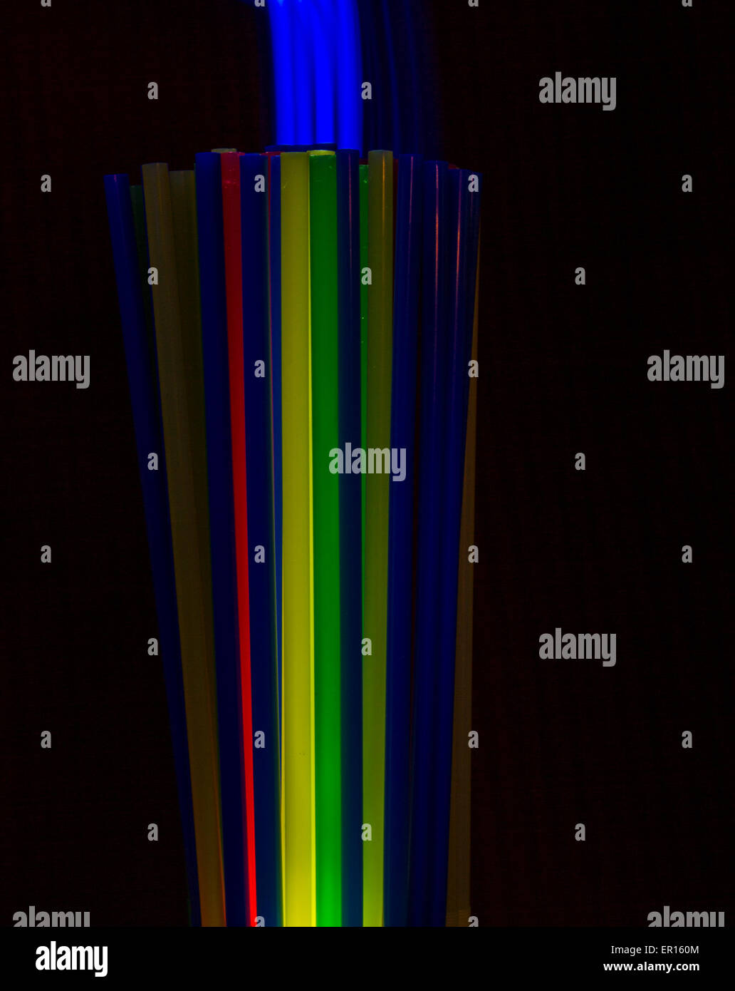 straws with bright blue light painting smoke standing vertical straight and colorful - Stock Image