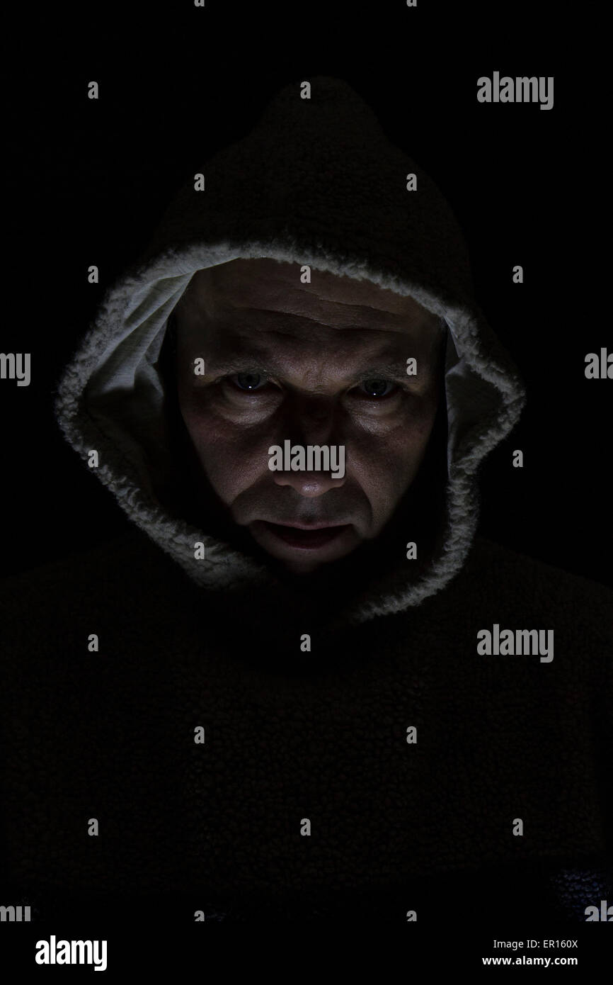 man with hood with one light and shadows with dark background - Stock Image