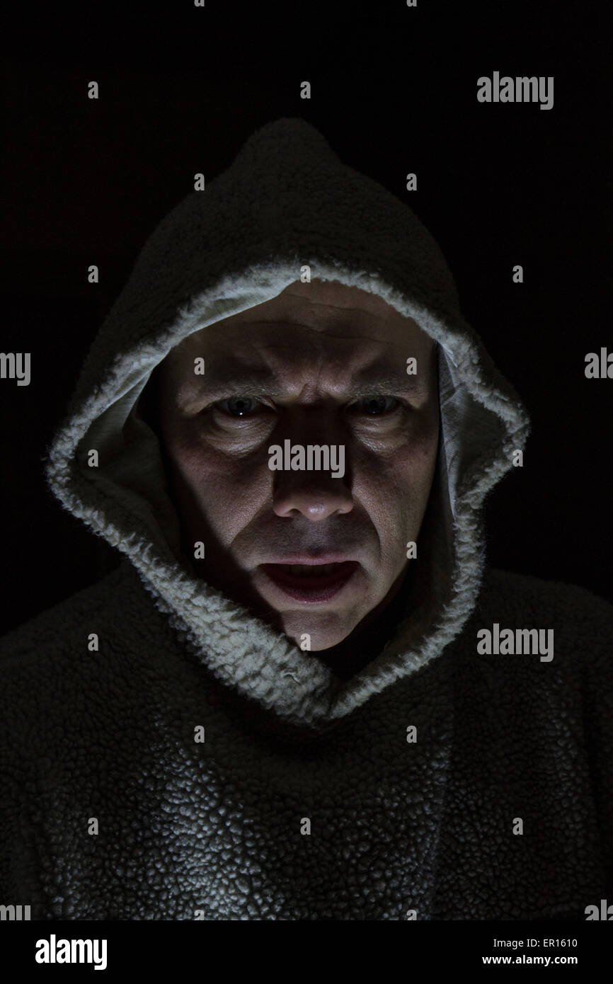 scary man with hood looking mean with dark background and face lit - Stock Image