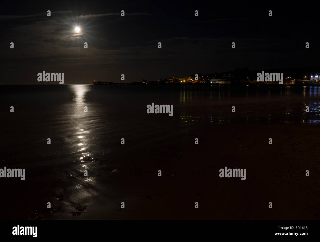 full moon shimmering over water in bay - Stock Image