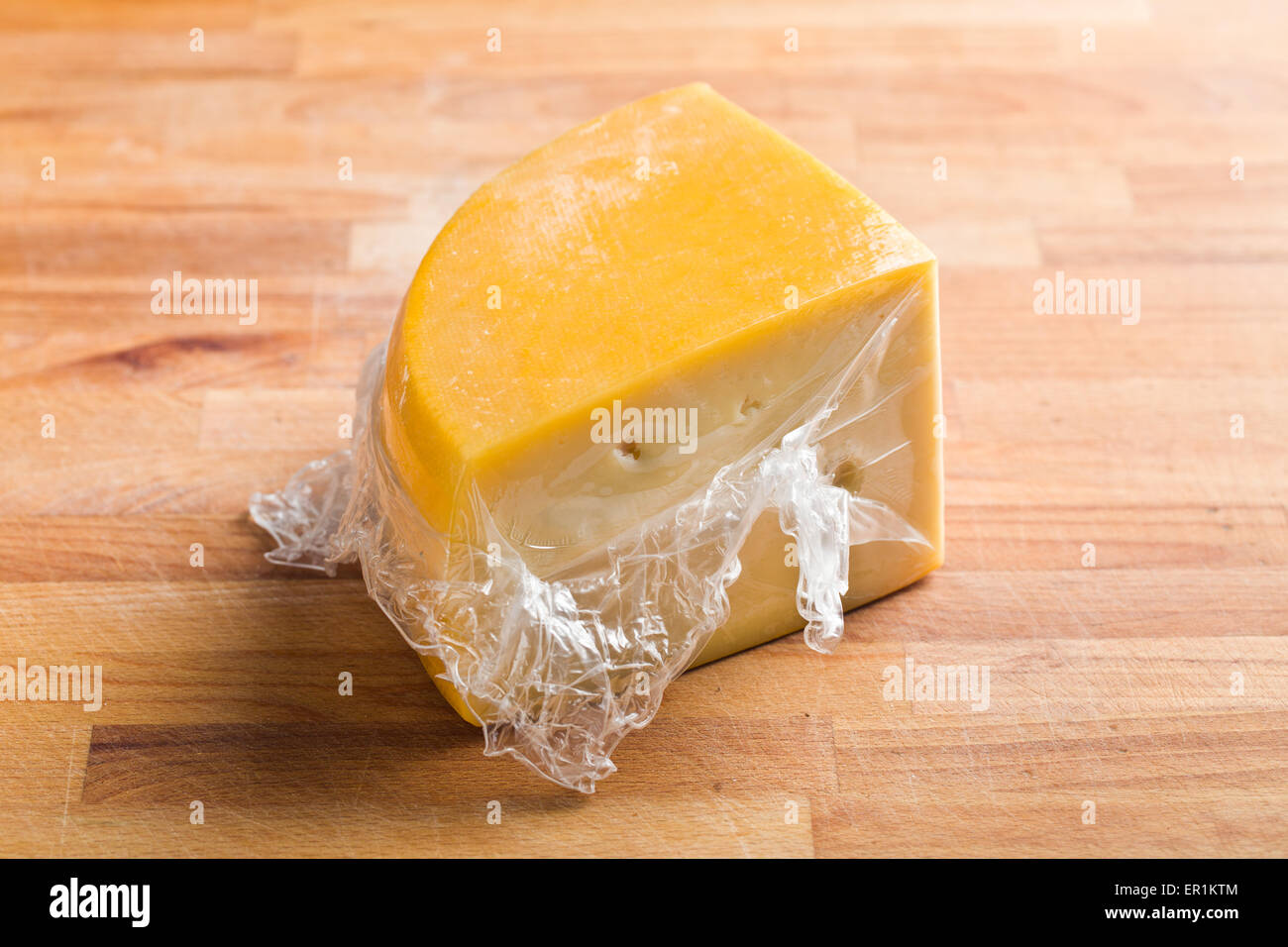 wrapped edam cheese on kitchen table - Stock Image