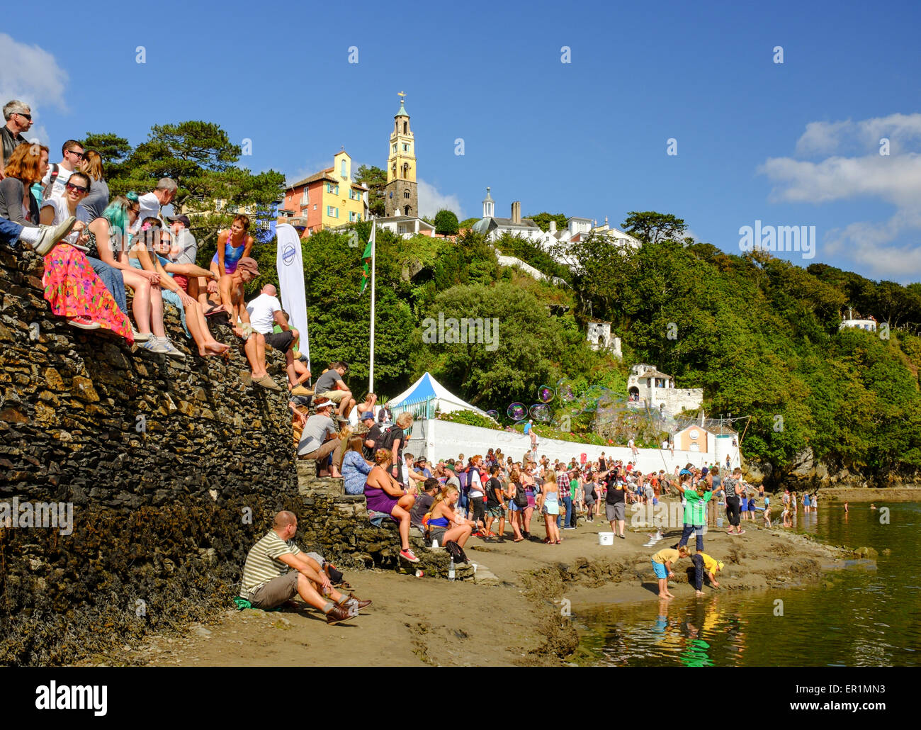 Festival attendees and families enjoying sunshine on the beach, during Festival No.6. In Portmeirion, North Wales Stock Photo