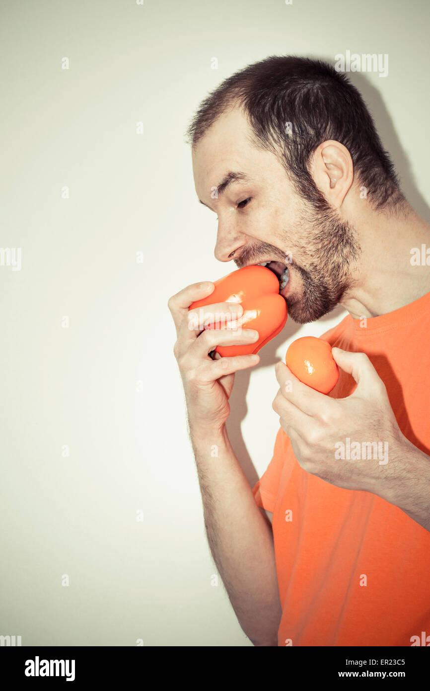 man (40 years) holding biting orange bell pepper mandarine hungry - Stock Image