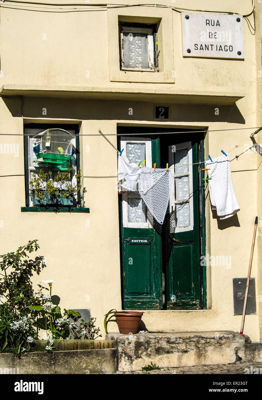 House in Lisbon showing washing and songbird in cage - it was singing beautifully as  I walked past. - Stock Image
