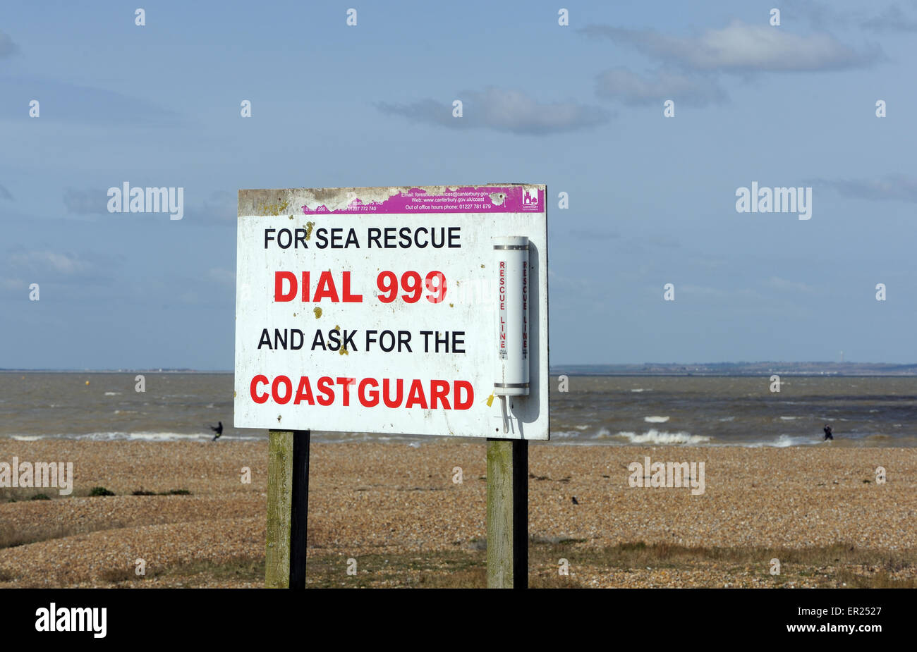 A sign on the beach at Whitstable saying dial 999 for the coastguard. Whitstable, Kent, UK. - Stock Image