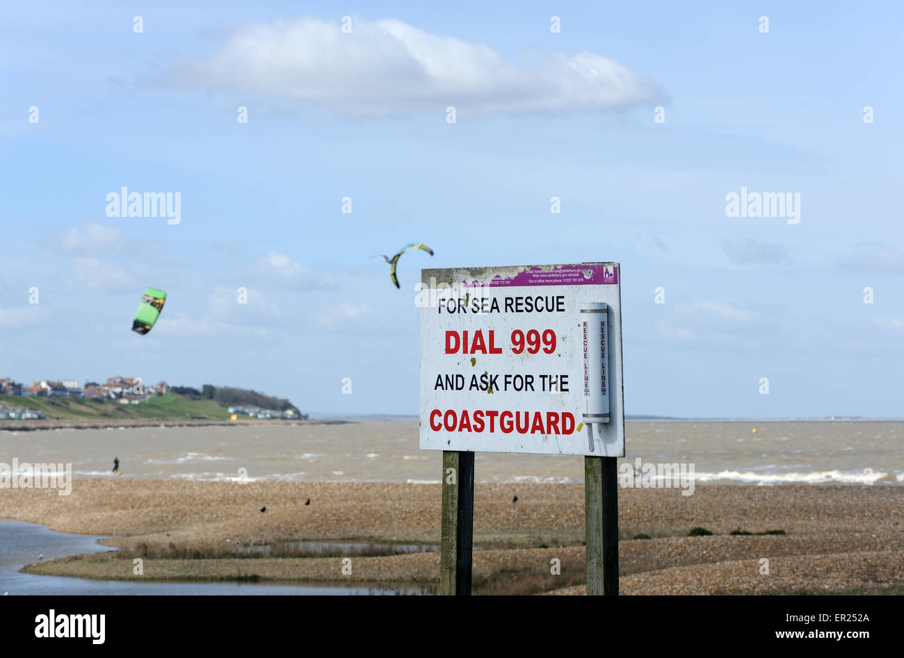 A sign on the beach at Whitstable saying dial 999 for the coastguard. Kitesurfers are in the background. Whitstable, - Stock Image