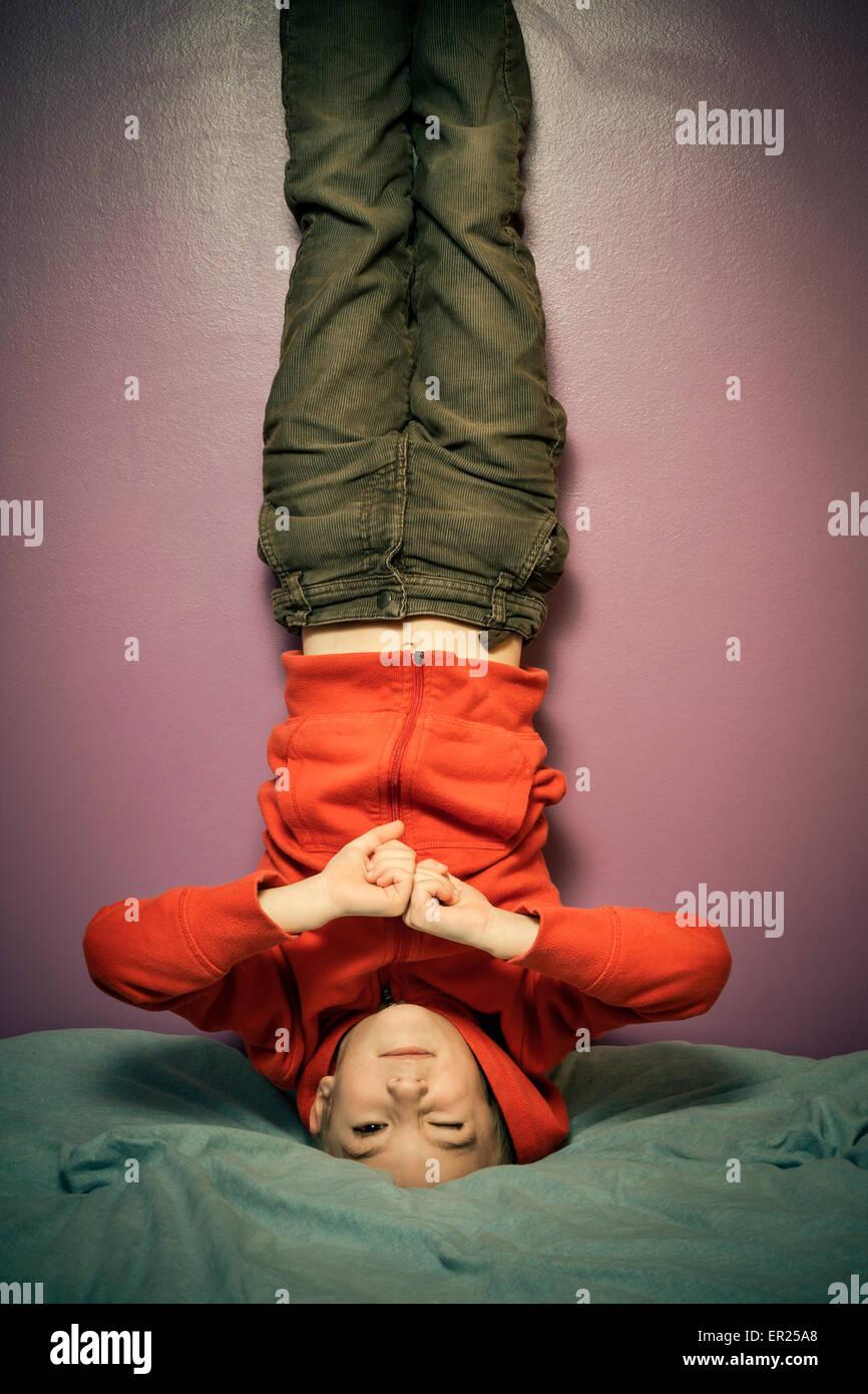 boy 8 years upside down bed bedroom - Stock Image