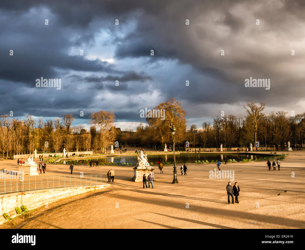 Paris, Tuilerires Garden - Bassin Octogonal pond, sculptures, sunlight and dramatic storm clouds - Stock Image