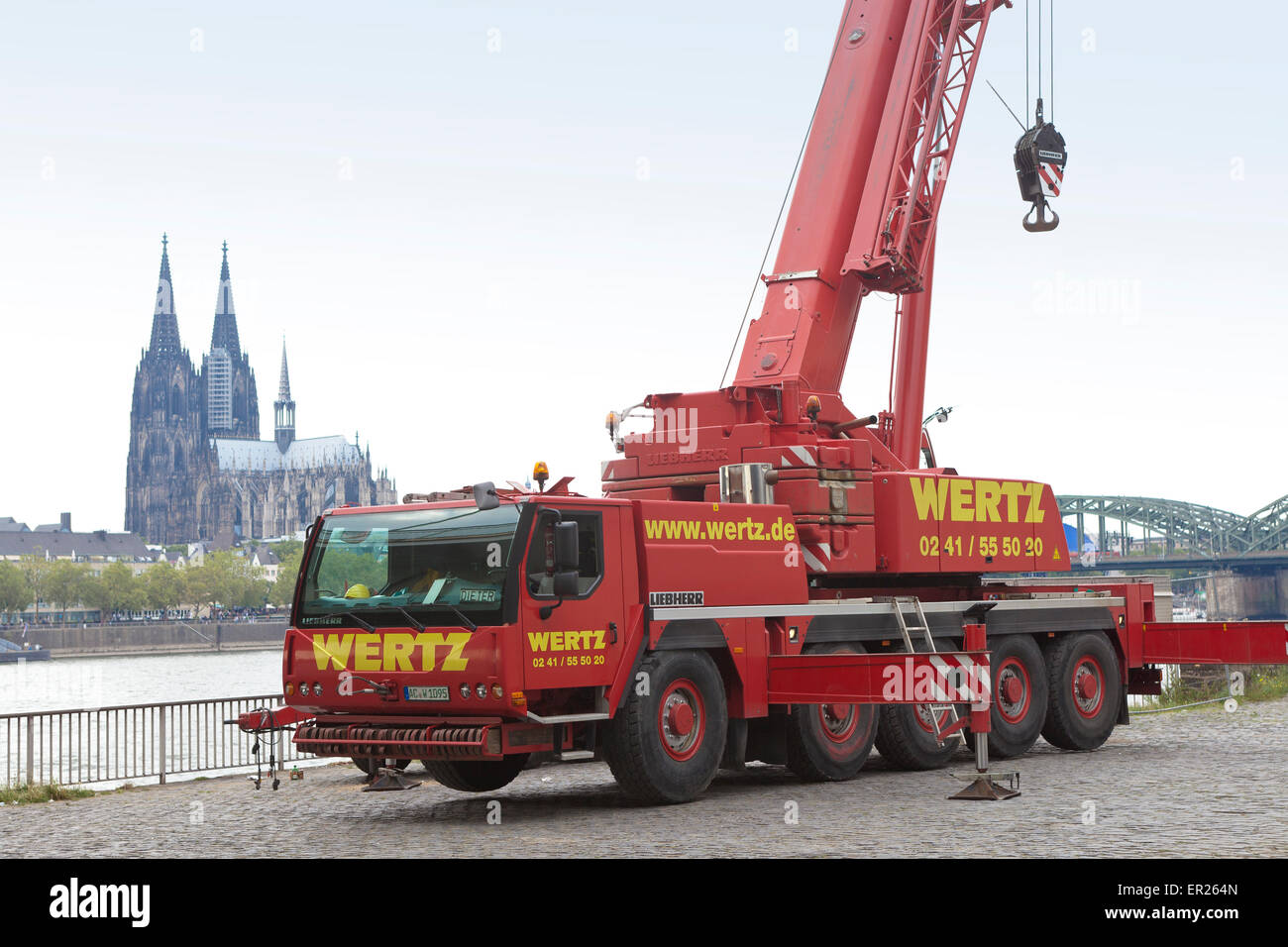 Europe, Germany, North Rhine-Westphalia, Cologne, truck-mounted crane of the company Wertz on the banks of the river - Stock Image