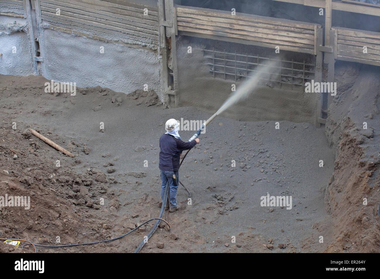 Europa, Deutschland, Nordrhein-Westfalen, Koeln, Grossbaustelle, Arbeiter traegt Spritzbeton fuer eine Spundwand Stock Photo