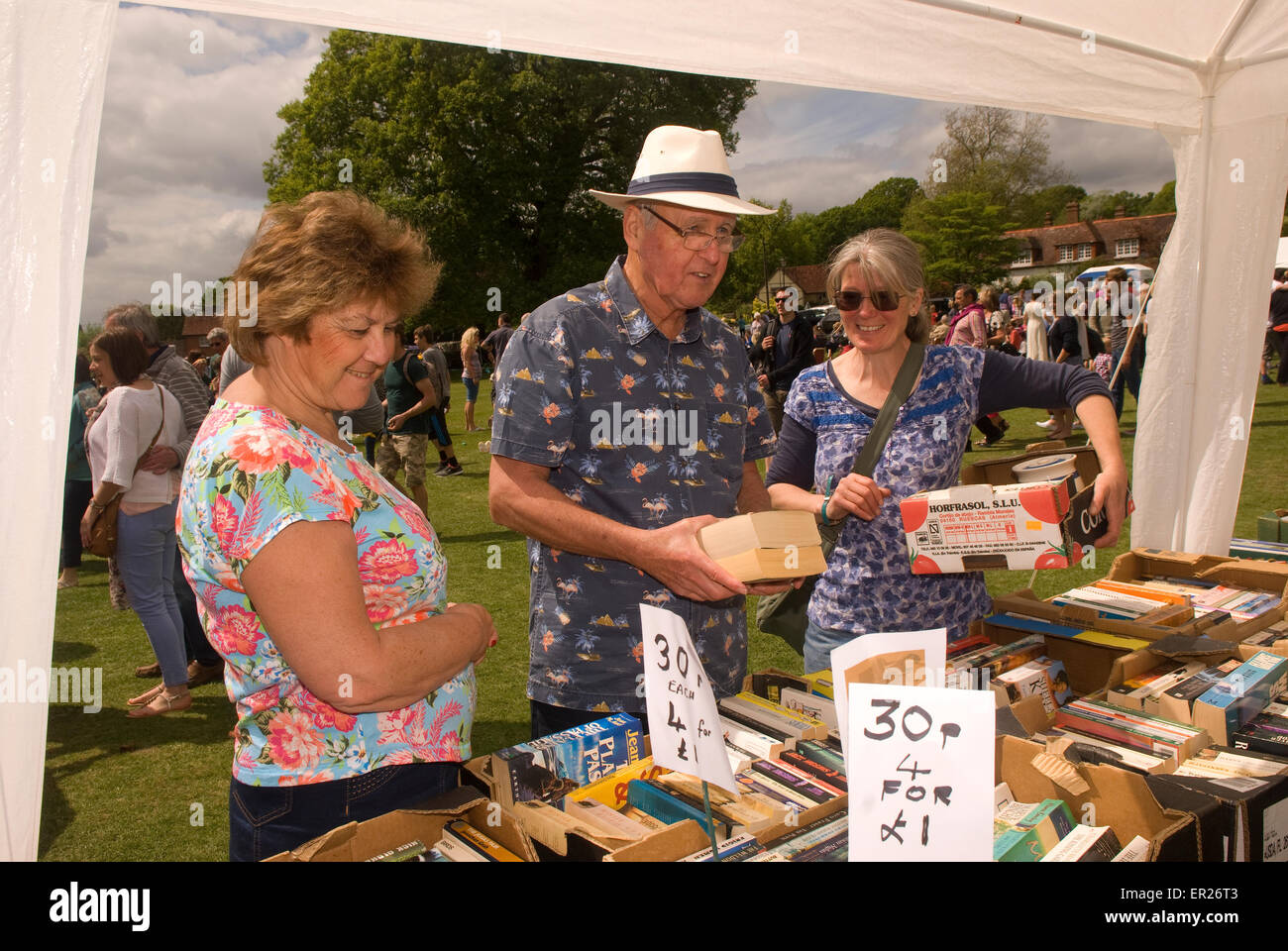 People browsing a book stall at Fernhurst Revels annual fair, Fernhurst, West Sussex, UK. - Stock Image