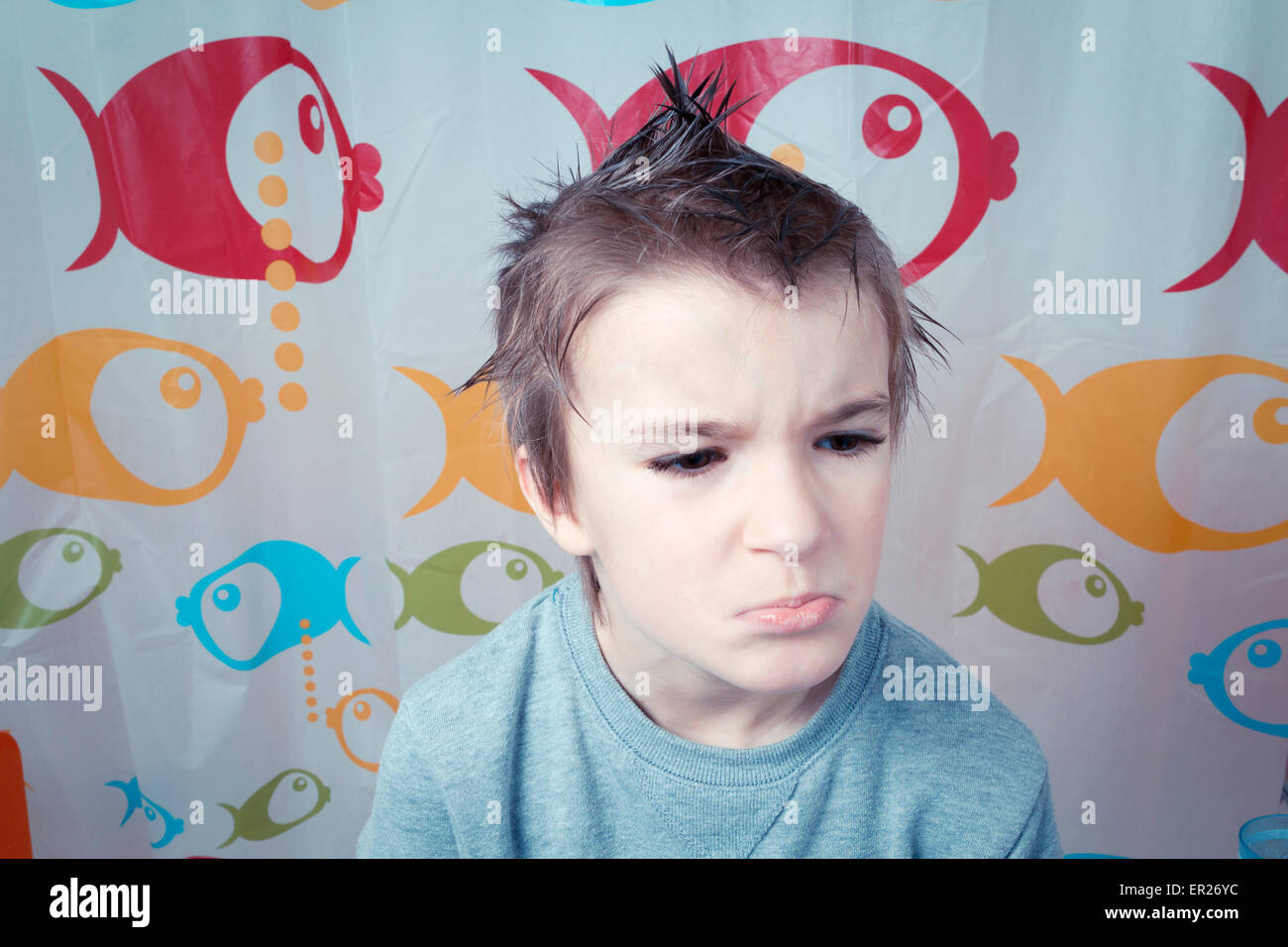 boy 8 years hairstyle spiky hair making a face - Stock Image