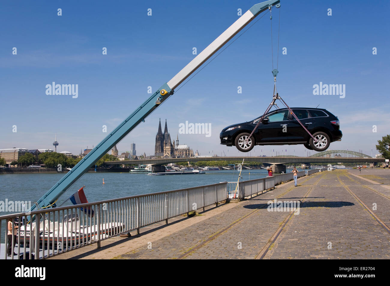 Europe, Germany, Cologne, a boatman at the bank of the river Rhine lands his car, in the background Cologne cathedral. - Stock Image