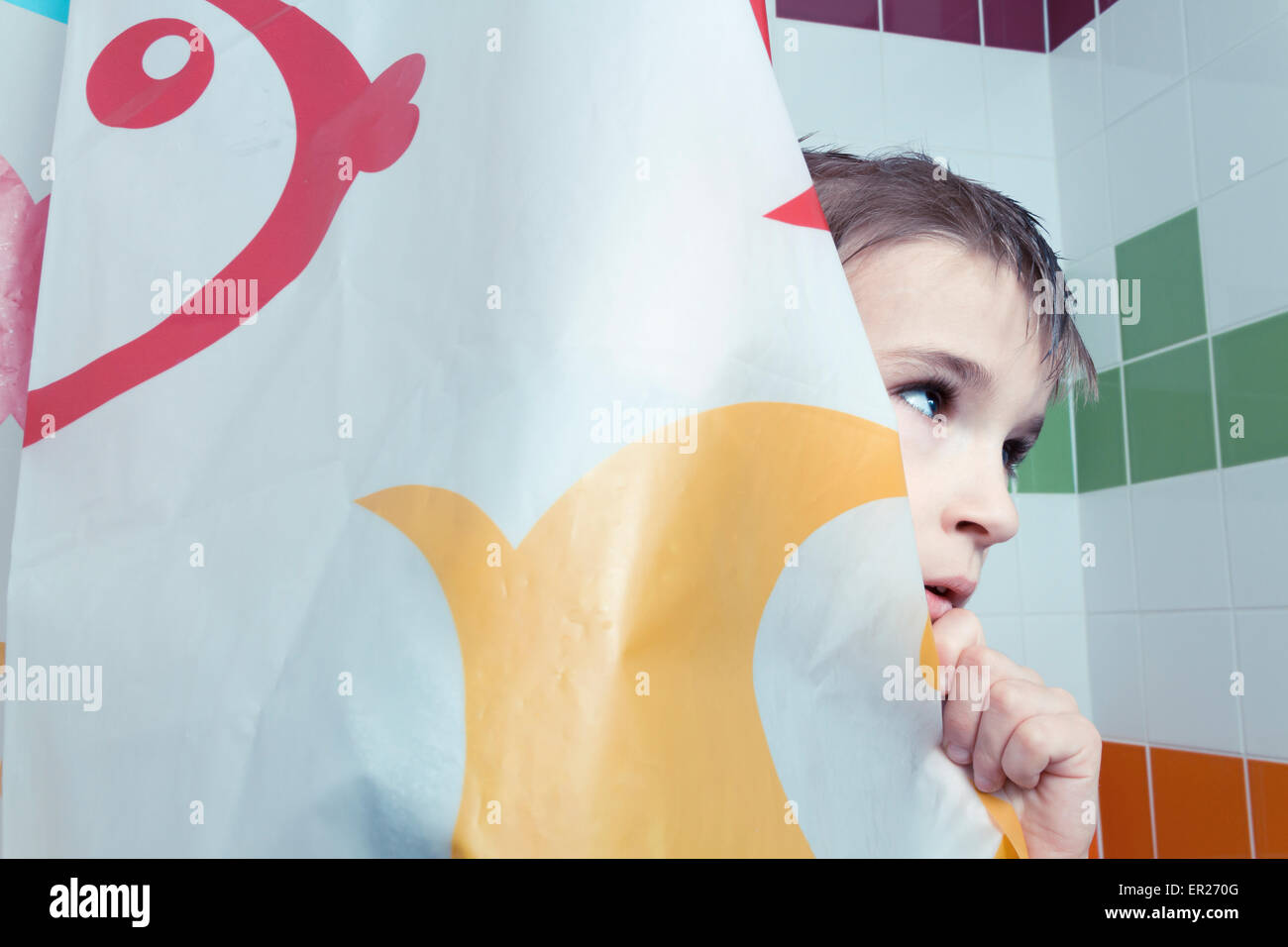 boy 8 years behind shower curtain - Stock Image