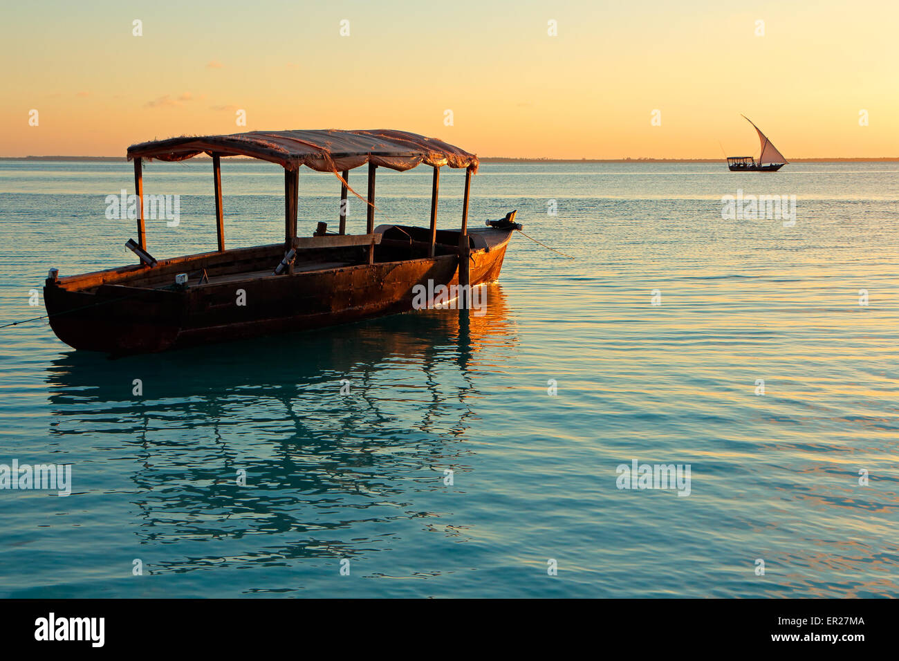 Wooden boat on water at sunset, Zanzibar island - Stock Image