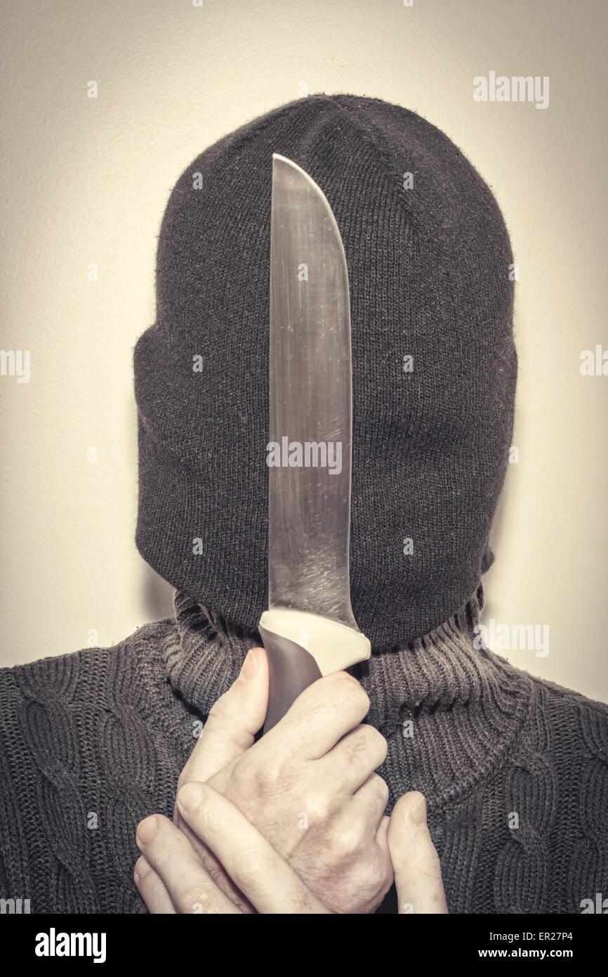 hidden man holding knife - Stock Image
