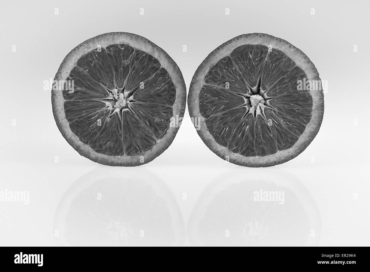 Two halves of an orange on the white and grey gradient background with orange's reflections on the bottom. High - Stock Image