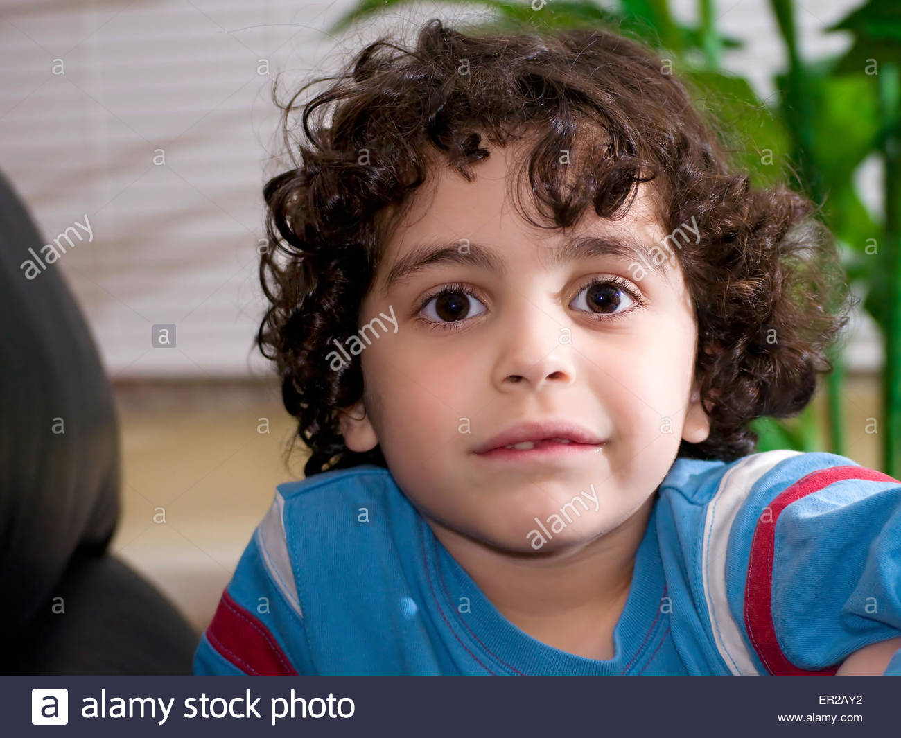 Adorable little boy with big brown eyes and curly dark hair and light fair skin smiles for the camera! - Stock Image