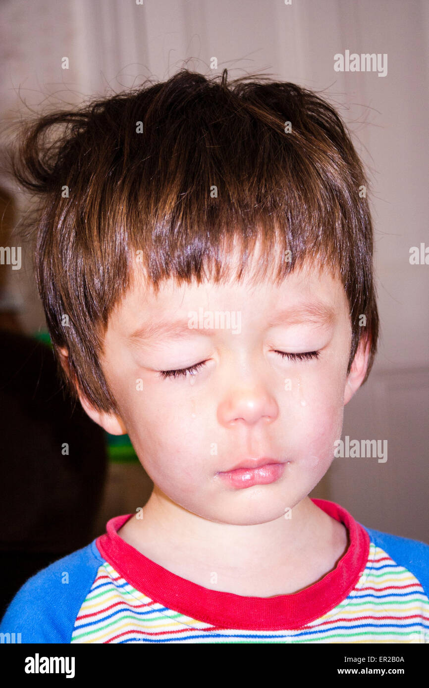 3 - 5 year old Caucasian child, boy. Facing, head and shoulder, crying, eyes closed shut - Stock Image