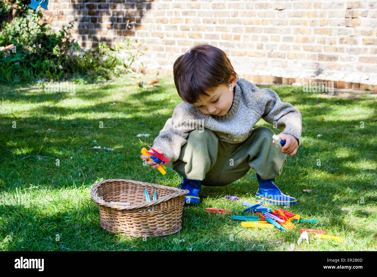 3 - 5 year old Caucasian child, boy. Crouching down outside in garden, putting clothes pegs into basket - Stock Image