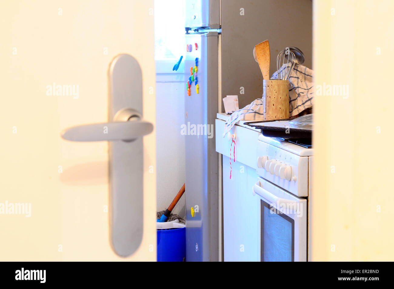 View throught slightly open door upen mess in domestic kitchen - Stock Image
