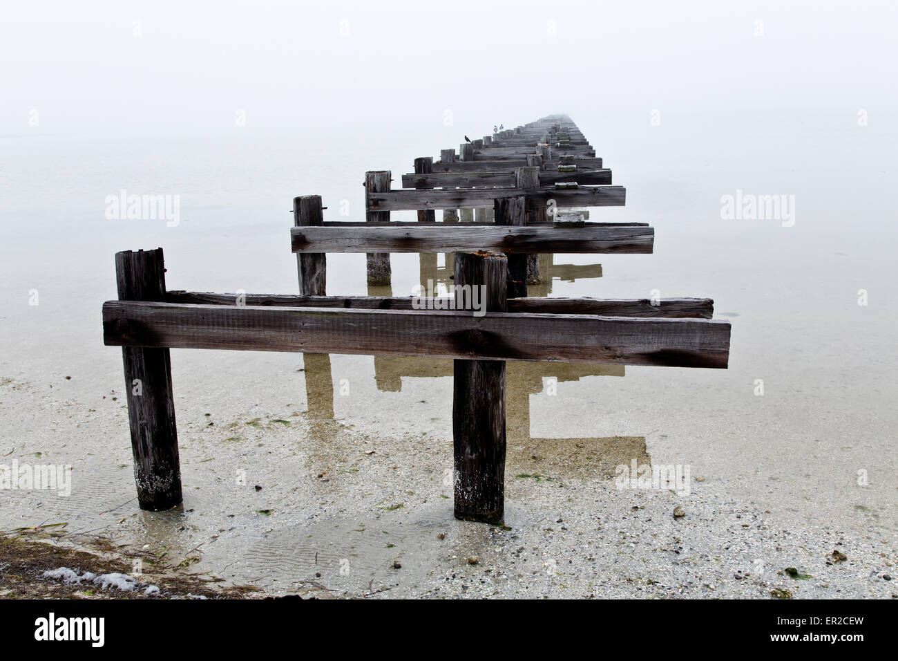 Abandoned  wood pier disappearing into foggy waterway. - Stock Image