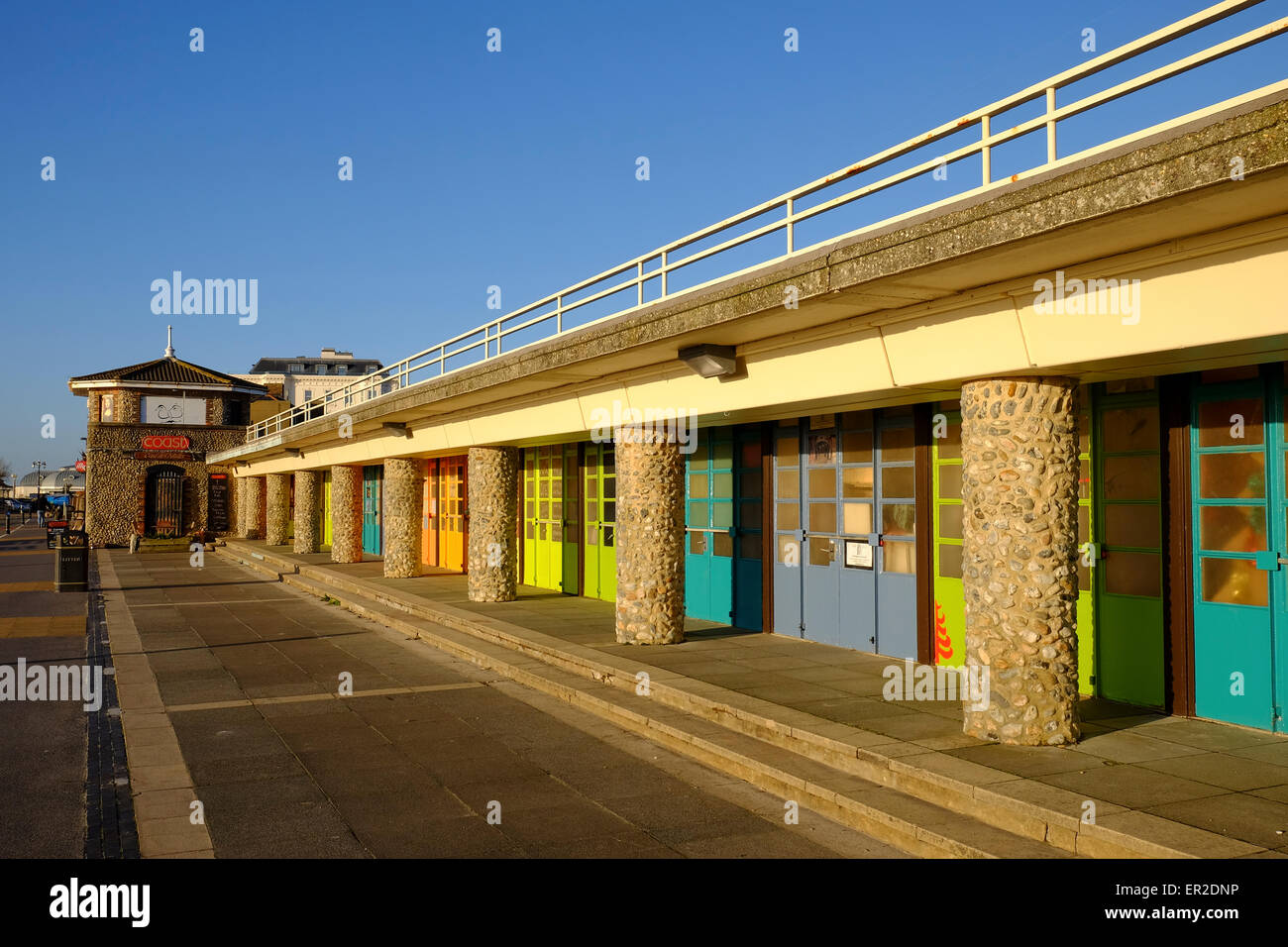 Brightly coloured artists lock-ups and coast cafe on the seafront at Worthing lit by the warm winter morning sunlight - Stock Image
